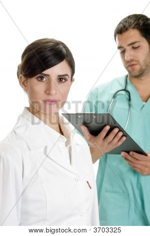 Busy Doctor Looking Writing Pad And Nurse Looking You