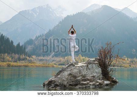 A Zen Man In White Practices Yoga In Nature. Pose Vrikshasana Or Tree Pose