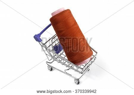 In A Shopping Cart Lies A Red Skein Of Thread On A White Background. Isolate
