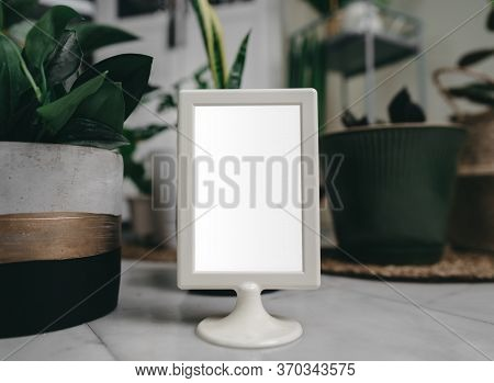 Hipster Mockup Image On Picture Frame Or Portrait Frame On Table.showing A Frame With Blank White Sc