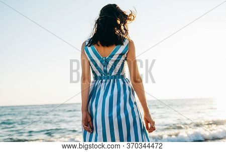 Horizontal Rear View Image Of Brunette Beautiful Young Woman Walking Along Beach And Sea At The Suns