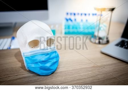 Human Skull Or Cranium Head Wearing Blue Surgical Mask With Test Tube Set And Computerl In Medical L