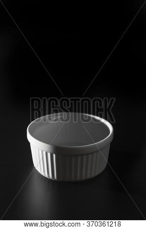 Empty White Ramekin On Black Background With Copy Space.
