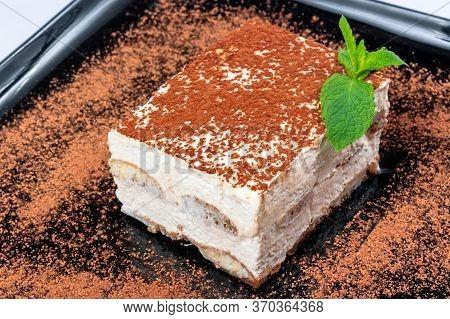 Traditional Rich Tiramisu Cake With Cinnamon On A Black Plate. Tasty Italian Dessert Decorated With