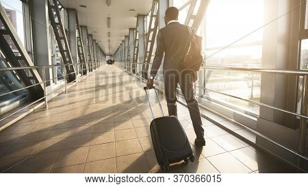 Business Trip. Unrecognizable African Businessman Walking With Travel Suitcase Back To Camera In Air