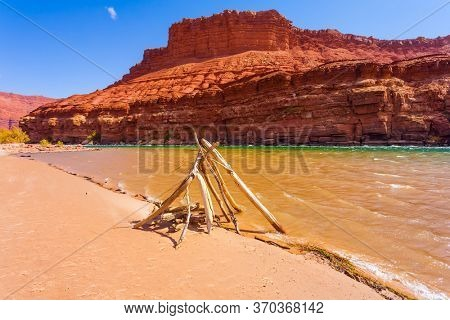 Dry branch construction by the river. The steep banks of red sandstone. Lee's Ferry is a historic boat ferry across the Colorado River. USA. The concept of active and photo tourism