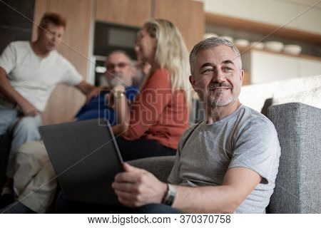 Mature man and his family spend their free time in their living room.