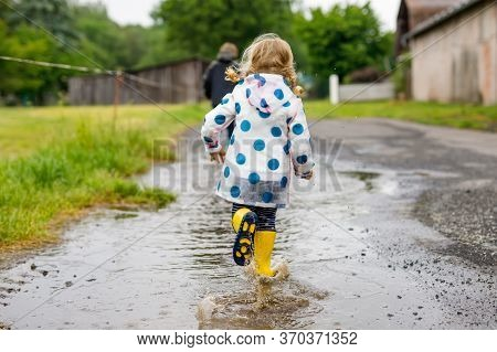 Two Children, Toddler Girl And Kid Boy Wearing Red And Yellow Rain Boots, Walking During Sleet. Happ