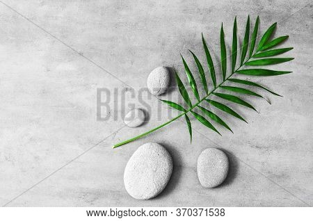 Flat Lay Composition With Spa Stones, Green Palm Leaves On Grey Background.