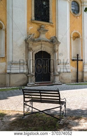 Entrance To The Saint Stephen (svaty Stefan) Baroque Church. Cross Beside The Door. Bench To Relax.