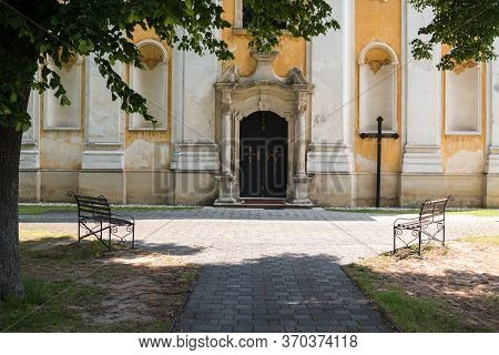 Entrance To The Saint Stephen (svaty Stefan) Baroque Church. Cross Beside The Door. Benches To Relax