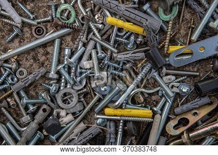 Old Steel Bolts And Nuts, Hooks And Yellow Dowels On Grunge Stone Background With Copy Space. Soft F