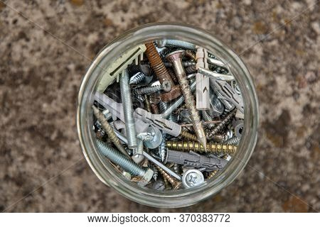Soft Focus To Assorted Hardware Bolts And Nuts In Glass Jar With Blurry Grunge Stone Background And