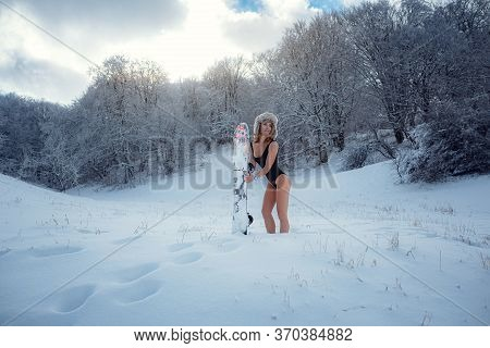 Attractive Woman Dressed In Swimsuit With Snowboard On The Slope