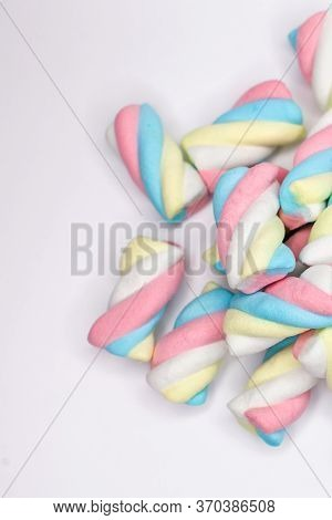 Top View On Colored Marshmallows Candies On A Wight Background. Concept Of Sweet Food And Desserts.