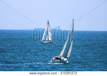 June 7, 2020 In Huntington Beach, Ca:  Sail Boats Riding The Natural Sea Breeze Including A Cargo Sh