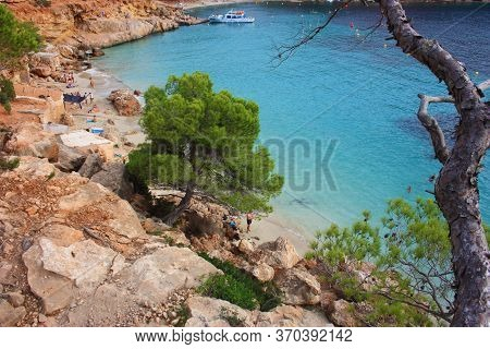 The Summer Tourist Destination Of Cala Saladeta Between Sea And Wild Nature And Trees And Crystal Cl