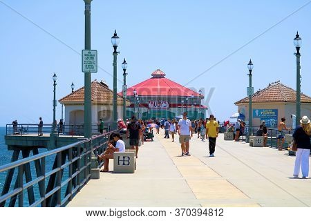 June 7, 2020 In Huntington Beach, Ca:  People Walking On The Pier With A Restaurant At The End Taken