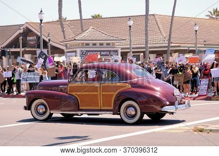 June 7, 2020 In Huntington Beach, Ca:  Vintage Wood Vehicle Named The Woody On A Street Besides A Bl