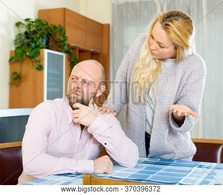 Family Quarrel. Sad Adult Man And Girl During Quarrel In Living Room At House .couple Having Problem