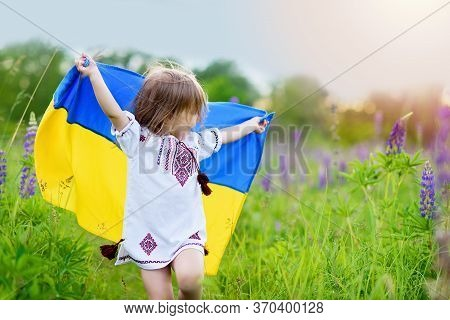 Child Carries Fluttering Flag Of Ukraine In Field. Ukraine's Independence Day. Flag Day. Constitutio