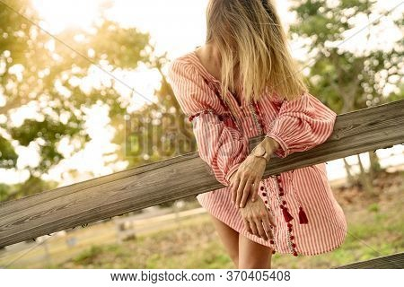 Beautiful bohemian woman with windswept hair leaning on rustic fence