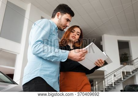 Couple Looking At Car Dealership Journal. Man And Woman In Car Dealership