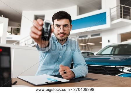 Auto Salesman Shows A Car Key While Sitting At A Table In A Auto Showroom