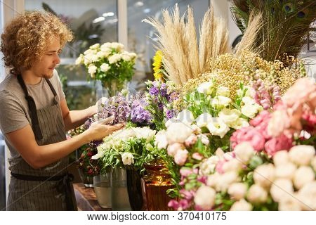 Young florist trainee takes care of the fresh cut flowers