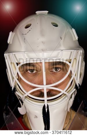 Detail Of A Male Face In A White Goalie Hockey Mask And  Colorful Lights.this Is A Detail Hockey Goa
