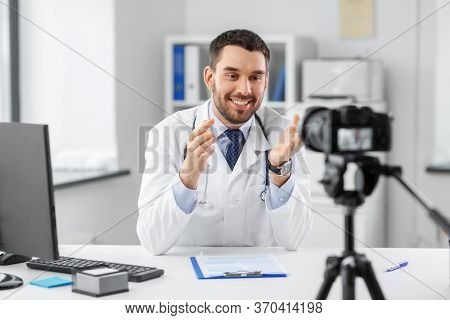 healthcare, medicine and blogging concept - happy smiling male doctor with camera recording video blog at hospital