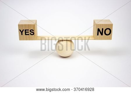 Yes And No Inscription On Wooden Cubes That Stand On A Wooden Swing On A White Background. The Conce
