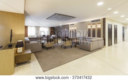 Lounge Area For Visitors With Large Gray Sofas And Armchairs In Hotel