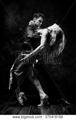 Dance and love concept. Young couple in elegant evening dresses in room filled with dramatic light. Two dancers man and woman holding each other in passionate pose. Black and white, monochrome.