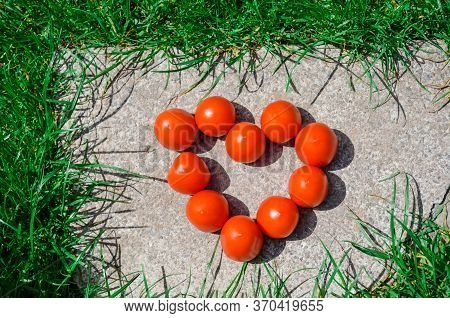 Heart Shape Formed With Freshly Picked Tomatoes. Fresh Tomatoes In The Form Of Heart In The Grass In