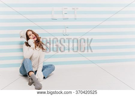 Joyful Caucasian Lady In Gray Socks And Trendy Jeans Posing With Smile On Striped Background. Studio