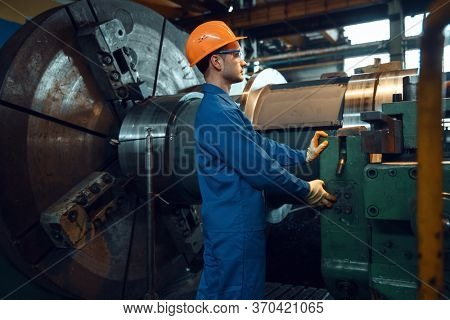 Male worker starts turning lathe on factory