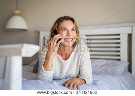 Portrait of beautiful happy woman talking with friend on mobile phone and smiling. Young woman talking on cellphone at home. Young lady lying on bed with smartphone while looking outside with big grin