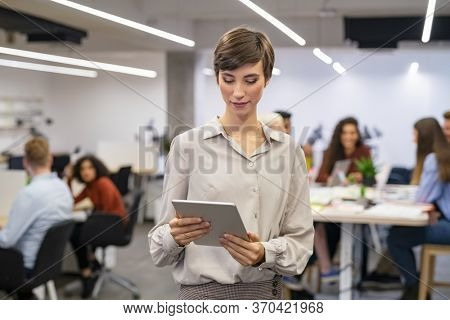 Happy young businesswoman using digital tablet in modern open office. Business woman typing on digital tablet with colleague working in background. Latin woman standing in a co working space working.