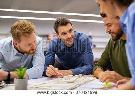 Group of creative people working together in office. Casual team of young architect and engineers working on scale model house. Mid adult man working on project while giving presentation to client.