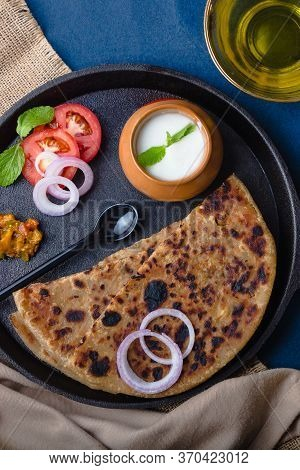 Aloo Paratha / Indian Potato Stuffed Wheat Bread Served With Curd & Pickle, Tomato & Onion. Top View