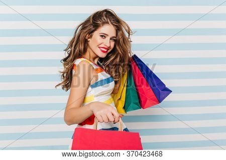 Happy Long-haired Woman Smiling After Shopping. Studio Portrait Of Pleased White Girl With Paper Bag