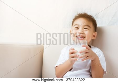 Close Up Of Happy Asian Little Cute Child Boy Hand Holding Milk Glass He Drinking White Milk During