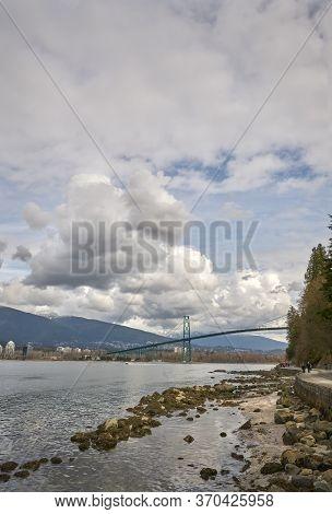 Lions Gate Bridge Burrard Inlet Vertical. The Stanley Park Seawall And The Lions Gate Bridge Over Bu