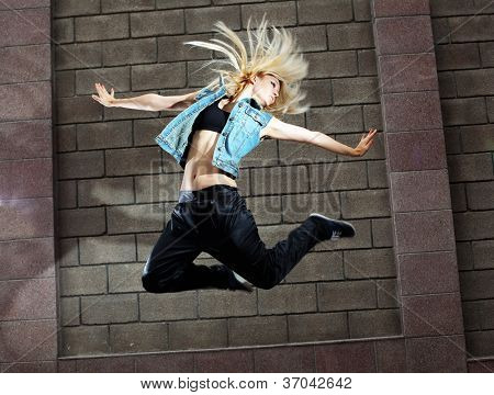 Teenage girl dancing hip-hop over the street wall poster