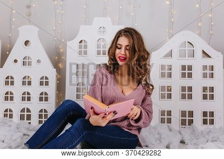 Portrait Of Young Girl With Curly Hair In Lilac Sweater Reading Book With Enthusiasm While Sitting O