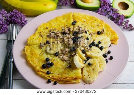 Tasty Pancakes With Bananas, Blueberries And Honey On Pink Plate. Close-up On White Wooden Table. Ho