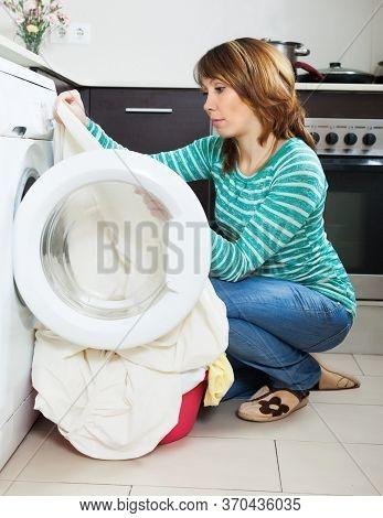 Sad Woman Cheking White Clothes Near Washing Machine At Home