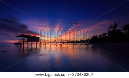 Amazing Beautiful Sunset With Silhouette Wooden Jetty And Coconut Tree