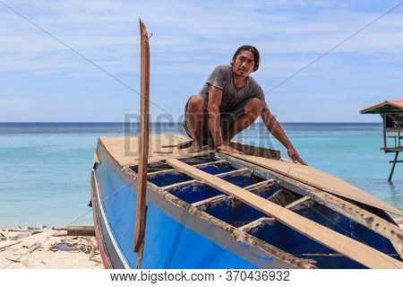 Unidentified Man Are Hardworking Repairing The Wooden Boat